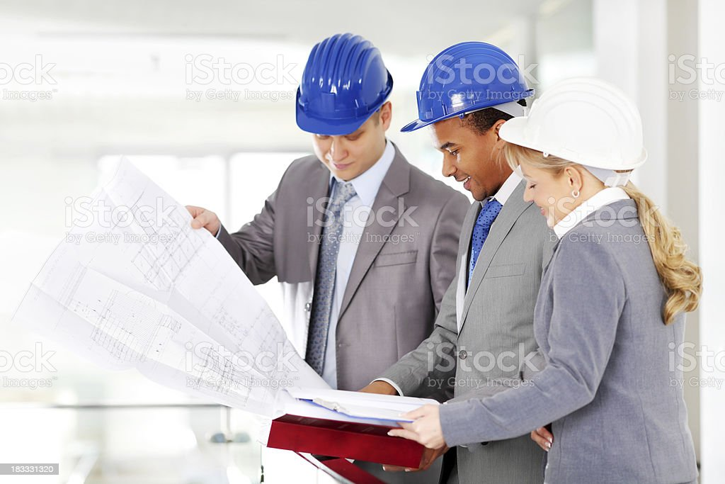 Small architect group are looking blueprints and building plans. royalty-free stock photo