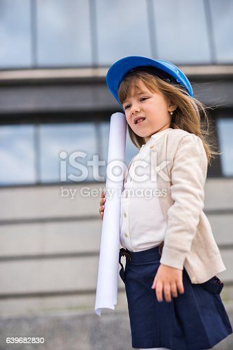 643843490istockphoto Small architect standing outdoors with blueprints. 639682830