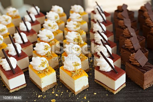 Small chocolate and vanilla layered cakes in rows on candy buffet. Sweet paradise.