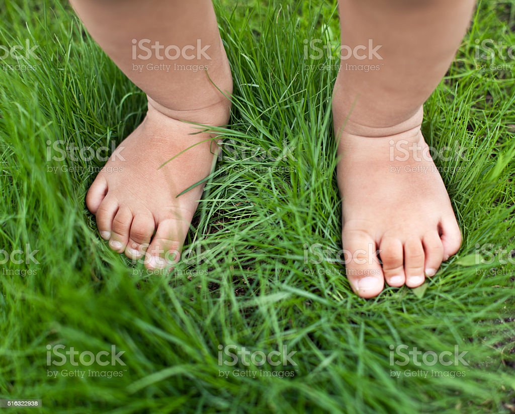 Small baby feet on the green grass. stock photo
