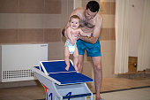 istock Small baby girl is swimming in the pool. Dad bathes a little girl in the pool 1212286268