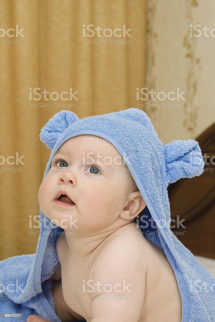 Маленький ребенок в голубой полотенце на кровати Стоковые фото Стоковая фотография