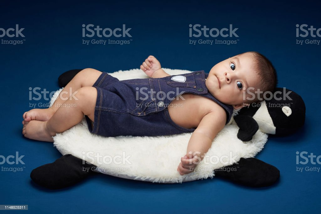 Small baby lay on pillow isolated on blue studio background