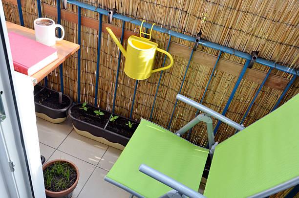 BALCÓN PEQUEÑO, pequeñas plantas en ollas cerca de verde silla - foto de stock