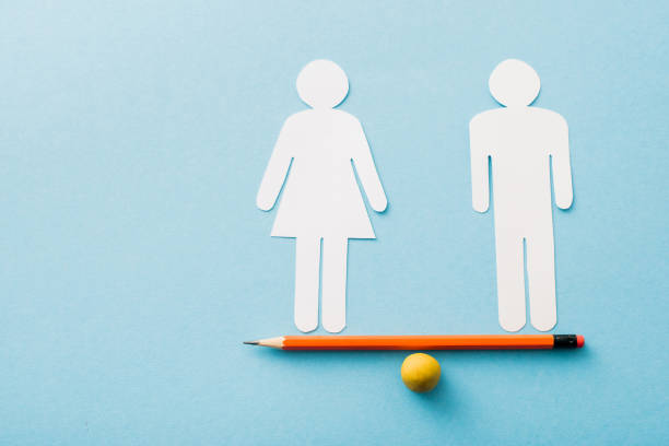 small ball and pencil with paper cut of couple isolated on blue, sexual equality concept stock photo