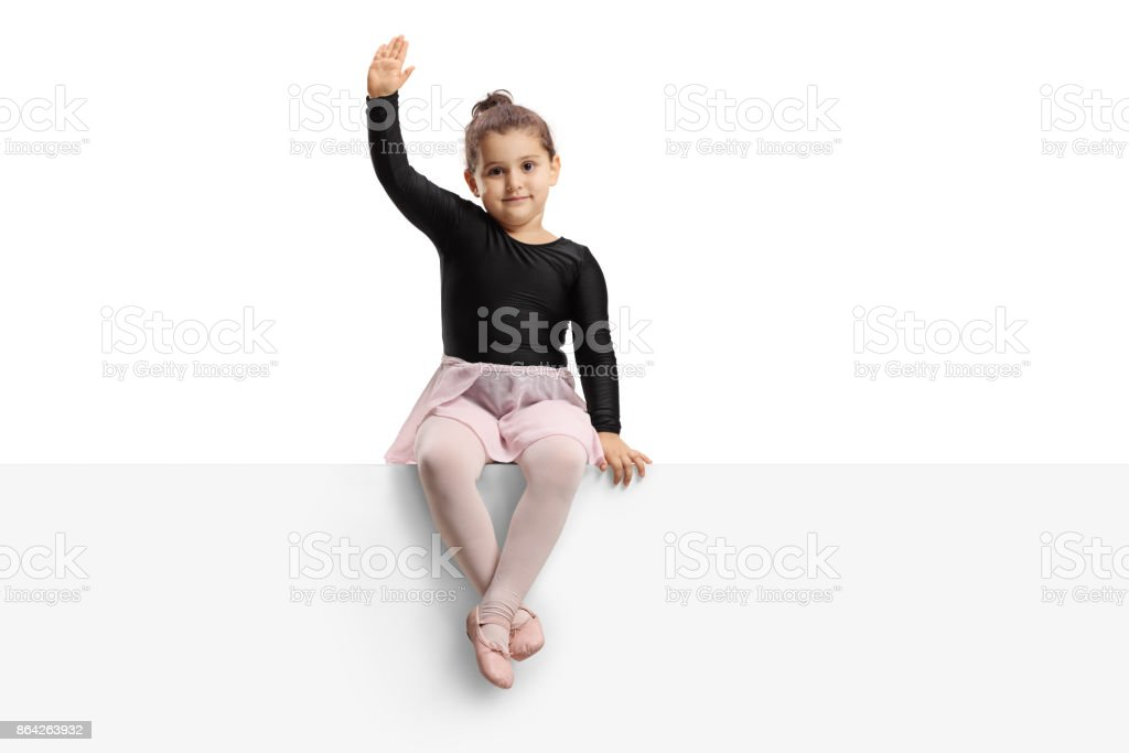 Small ballerina sitting on a panel and waving royalty-free stock photo