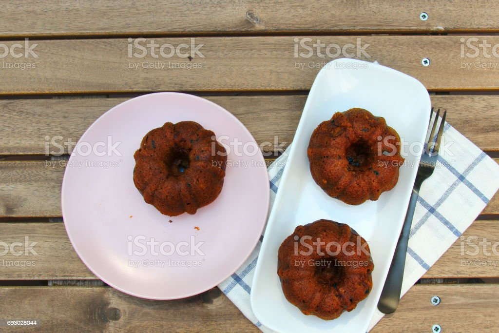 Small banana and dates bread Bundt cakes on a wooden background with copy space stock photo