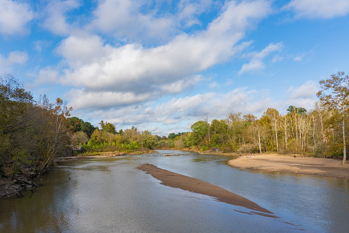 A small beach for fishing and relaxing on the banks of the Neuse River in Raleigh, North Carolina in autumn surrounded by trees near the Milburnie Dam bridge; landscape