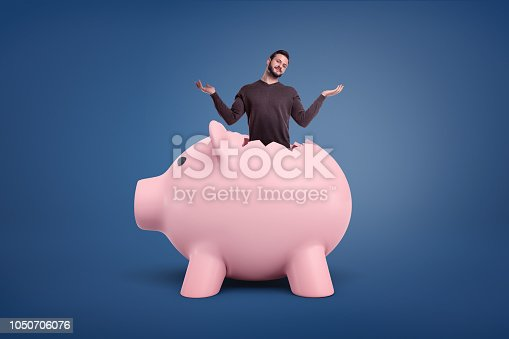 istock A small bearded man with a confused appearance sticks out from a crack in a giant pink piggy bank. 1050706076