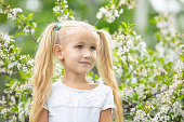 Small beautiful child girl portrait on the background of a flowering tree in spring