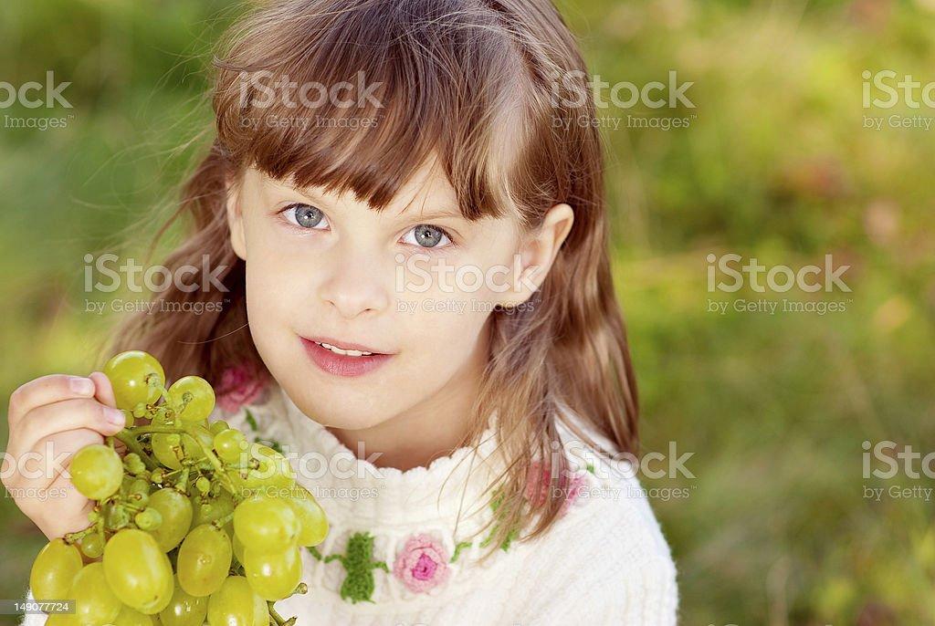 Small beautiful girl eats green grapes royalty-free stock photo