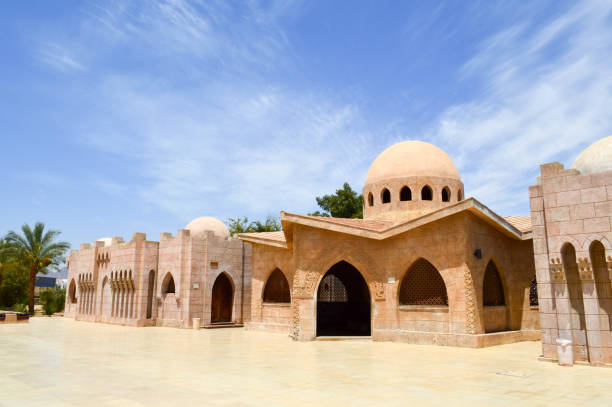 Small beautiful neat old ancient stone clay Arab Islamic Muslim houses with round domes in the desert with palm trees in a tropical country stock photo