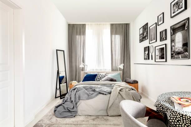 벽에 킹 사이즈, 거울, 흑백 사진이있는 작은 침실 인테리어 - 작은 뉴스 사진 이미지