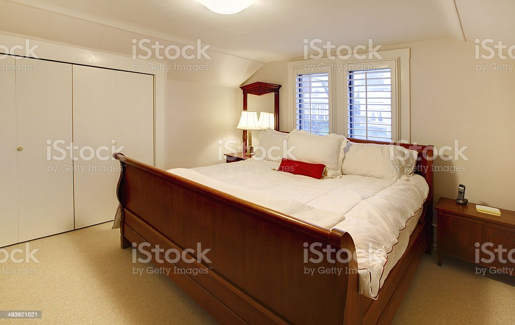 Small bedroom with large brown bed stock photo