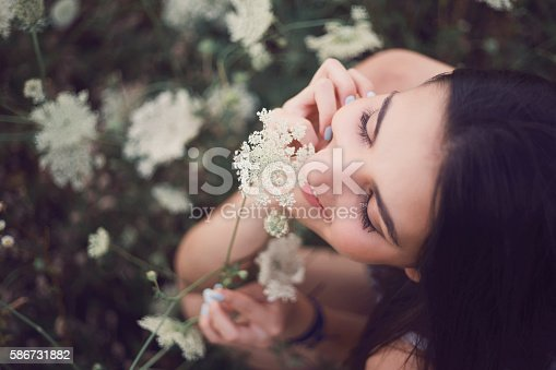 Beautiful young woman in a field of wild flowers.