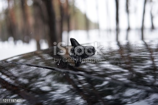 881639308 istock photo A small black antenna on the roof of a black car in the form of a shark fin. 1211197401