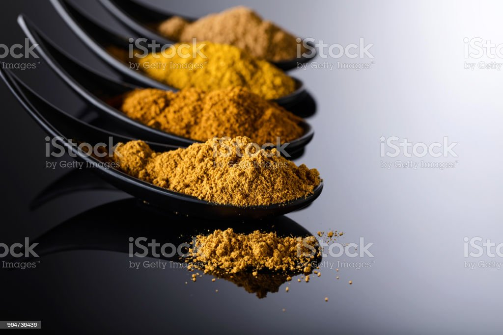 Small black bowls of Indian spices on black reflective background . royalty-free stock photo