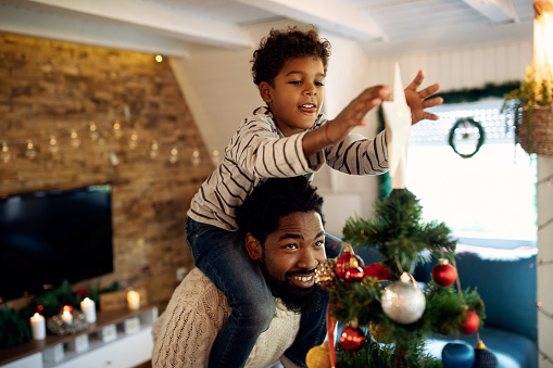Happy African American father carrying his son on shoulders and helping him to put star on top of Christmas tree.