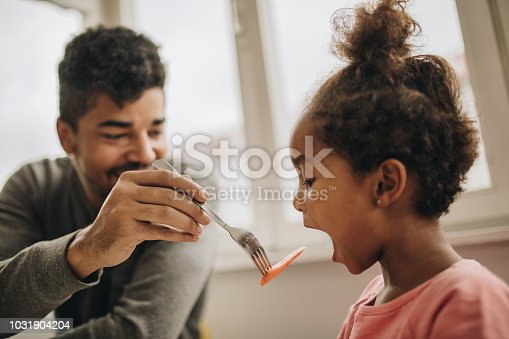 Happy black father feeding his daughter at dining table.