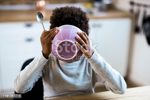Little African American boy eating breakfast from a bowl at dining table.