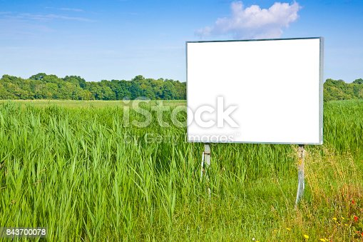istock Small blank advertising billboard in a green field - image with copy space 843700078