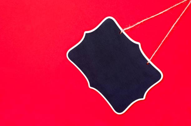 Kleine leere schwarze Tafel auf rotem Hintergrund. – Foto