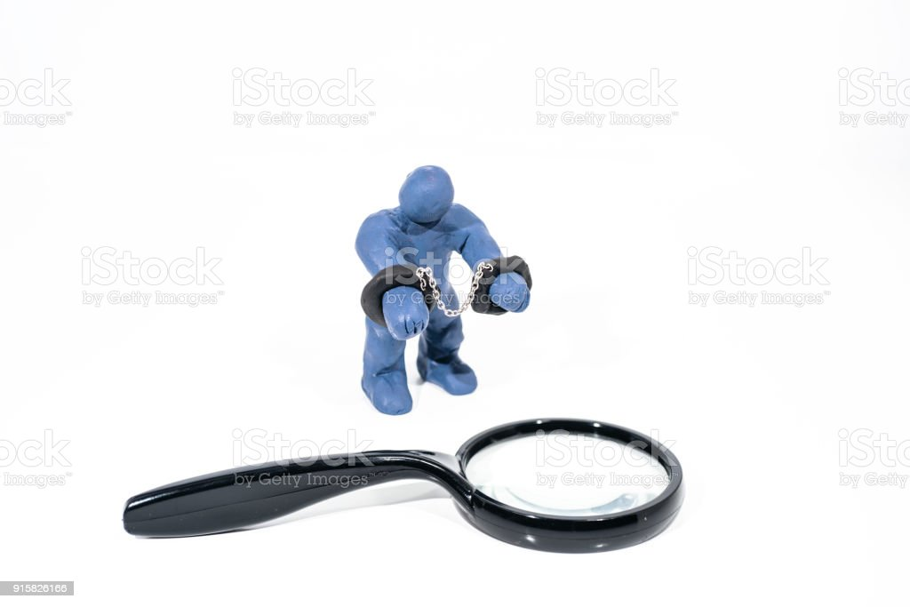 Small blue figure in handcuffs. Made from Play Clay. stock photo