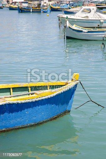 Small blue fishing boat in the clean water, water bay in Marsaxlokk, Malta's largest fishing village