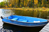 An image of a small blue fishing boat moored to a wooden dock.