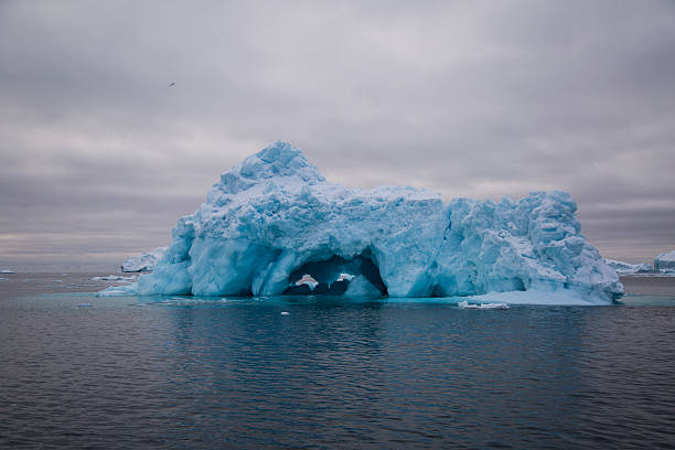 Small blue iceberg with cave stock photo