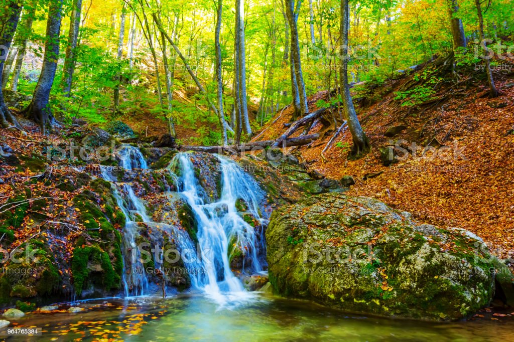 small blue waterfall on a mountain river at the autumn royalty-free stock photo