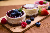 Small blueberry oval cheesecake with blueberry filling and berries decoration on wooden plate
