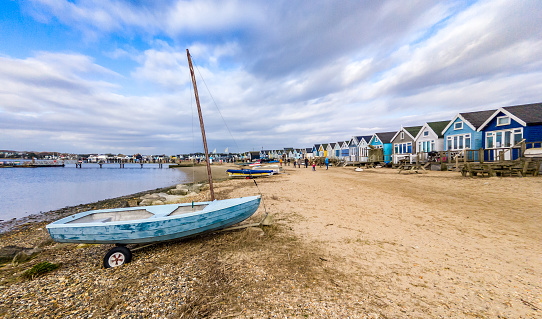 Small boat and beach huts at Hengistbury Head, Mudeford in Bournemouth