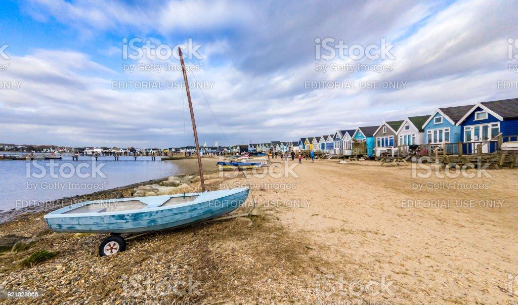 Small boat and beach huts at Hengistbury Head, Mudeford in Bournemouth stock photo