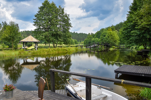 Small boat floating on a little lake, neat to wooden jetty, bridge and forest in the background