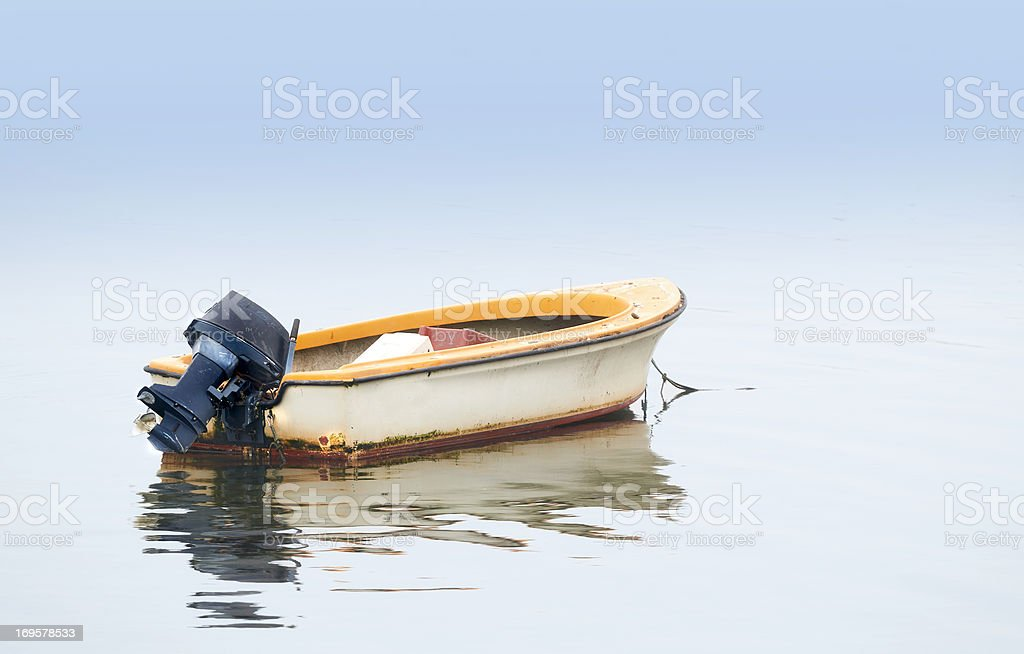 Small boat on an early foggy morning stock photo