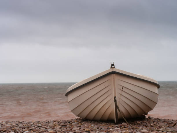 Small boat on pebble beach, aground. Winter. Not clinker. sailing dinghy stock pictures, royalty-free photos & images