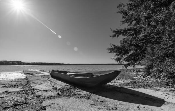 Small boat on pond bank. Artistic black and white scene stock photo