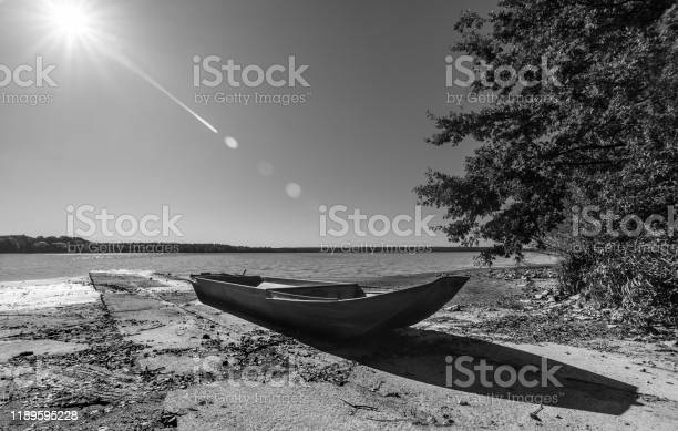 Photo of Small boat on pond bank. Artistic black and white scene