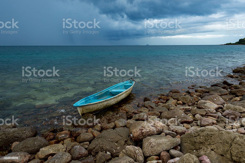 small boat on rock beah with rain storm stock photo