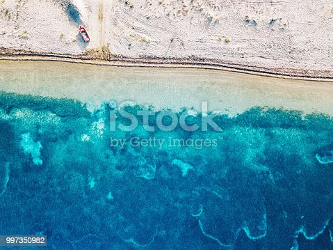 811600544 istock photo Small boat on the beach and tranquil sea waters 997350982