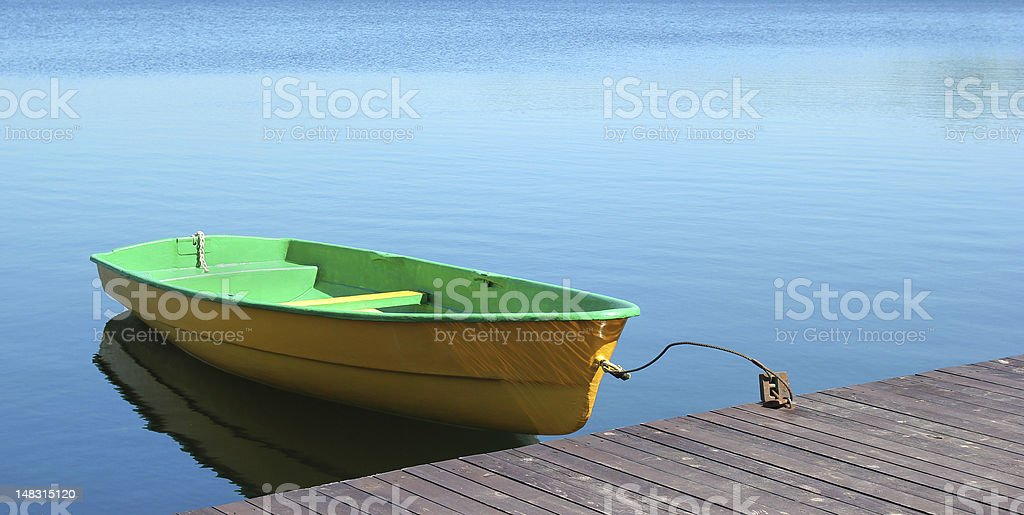 Small boat parking at a wood dock royalty-free stock photo