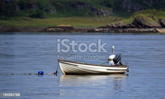 A small rowing boat with outboard motor. The picture was taken on the east coast of Scotland near Oban.