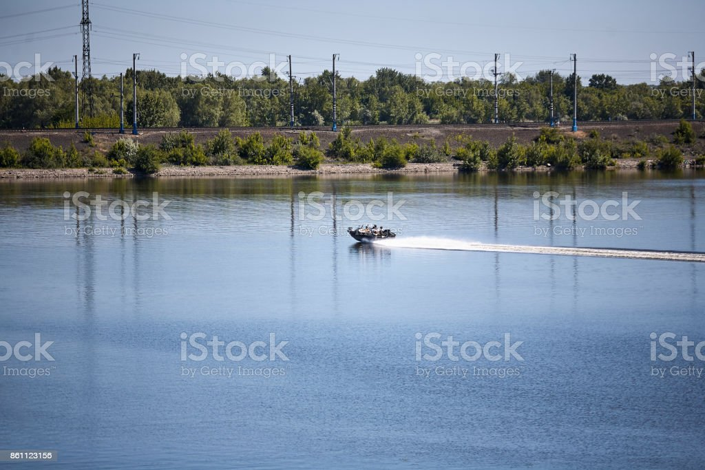 A small boat sails along the river on a summer sunny day stock photo