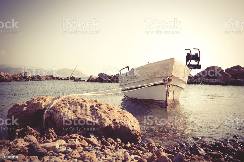 Small boat vintage style anchored to a rock royalty-free stock photo