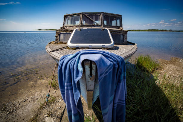 Small boat with beach towel on top of it stock photo