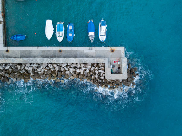 Small boats anchored by the concrete pier from above stock photo