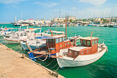 beautiful small white wooden fishing boats moored at port on sunny summer day in Iraklio, Crete, Greece