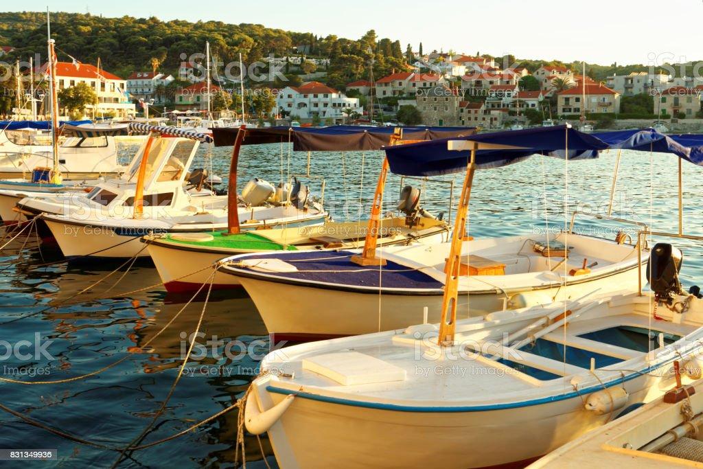 Small boats moored in the harbor of a town Postira - Croatia, island Brac stock photo