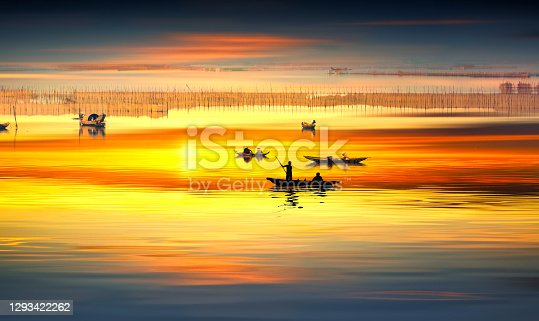 Small boats of fishermen move fishing in lagoon sunset sky, one of the largest lagoons in central Vietnam